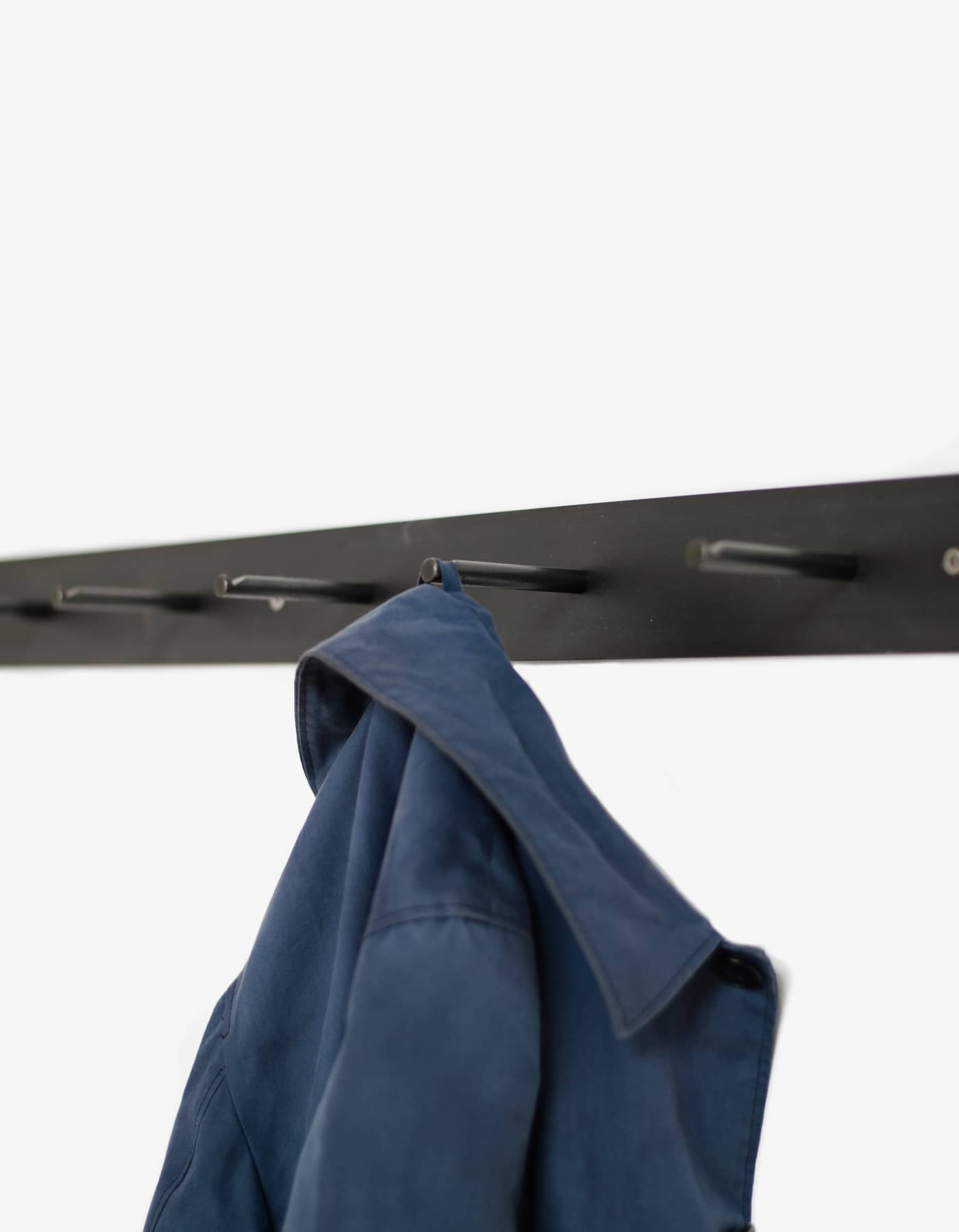 Hellogoodbye coat rack is made of a flat piece of crude steel plus six round hooks with notches to prevent clothes or coat hangers from sliding off.