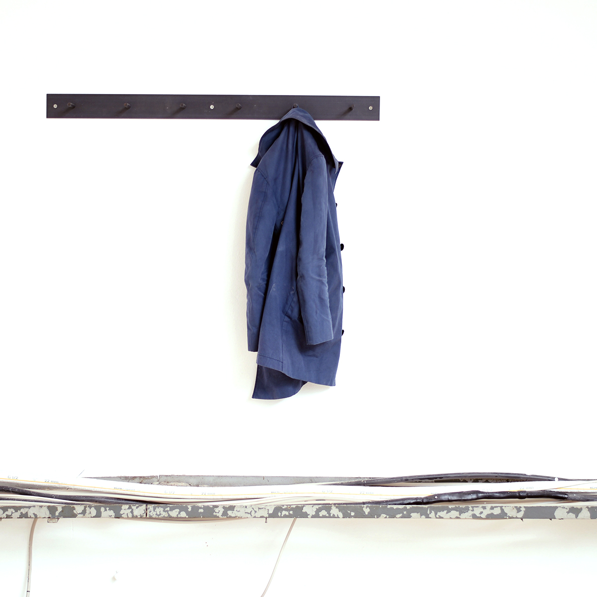 Hellogoodbye coat rack is made of a flat piece of crude steel plus six  round hooks
